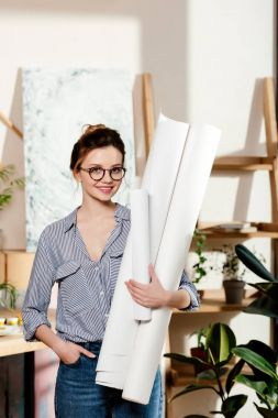 stylish young woman in eyeglasses holding canvases in studio