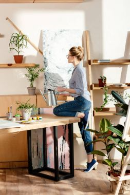side view of stylish female artist in eyeglasses watering potted plan in studio