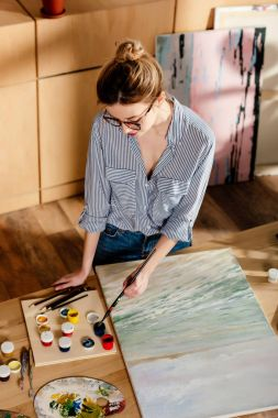 high angle view of stylish female artist in eyeglasses putting brush into paint