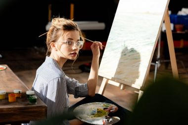 young stylish female artist in eyeglasses holding palette and paintbrush