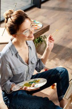 Smiling stylish female artist in eyeglasses holding palette and paintbrush stock vector