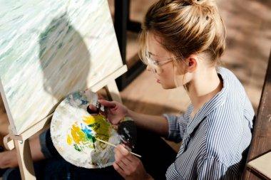 Side view of stylish female artist in eyeglasses using palette stock vector