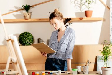 young female artist reading book and standing at table with painting supplies