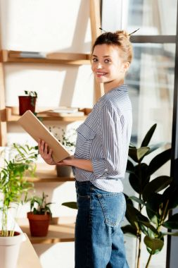 smiling young woman reading book near potted plants