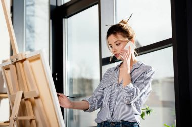 young female artist talking on smartphone and painting on easel