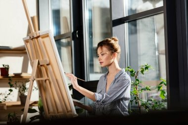 young female artist painting on easel in art studio