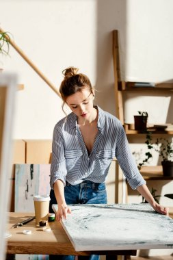 female artist looking at own painting on table with coffee cup