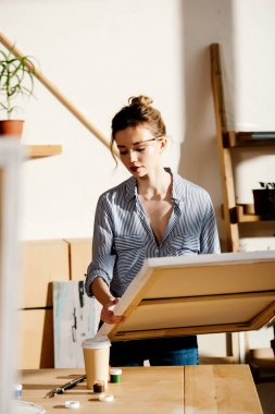 young female artist with canvas in hands in art studio