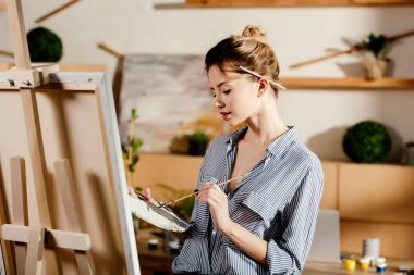 female artist with paintbrush behind ear drawing picture in studio