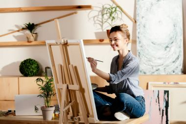 smiling female artist sitting on table and drawing on canvas in studio