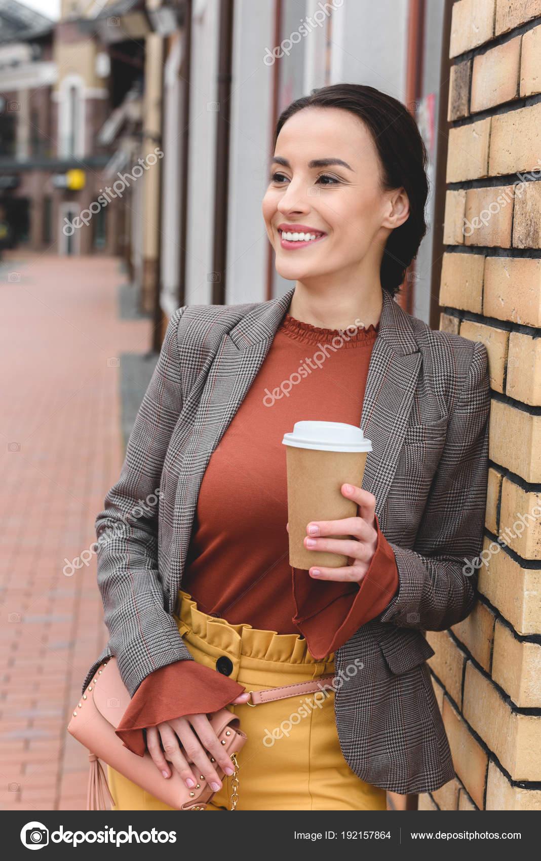 Happy beautiful stylish woman holding coffee paper cup leaning wall happy beautiful stylish woman holding coffee paper cup leaning wall stock photo voltagebd Images