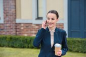 Fotografie beautiful businesswoman talking by smartphone and holding disposable coffee cup