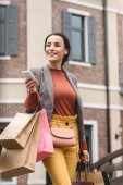 Fotografie atraktivní žena držící nákupní tašky papírové a smartphone