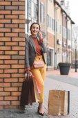 Fotografia donna attraente che si appoggia sulla parete dopo lo shopping e ne da smartphone