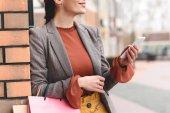 körülvágott kép nő smartphone és bevásárló táskák