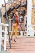 atraktivní žena chůze od obchodů a mluví o smartphone