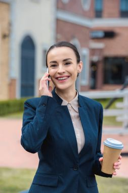 smiling beautiful businesswoman talking by smartphone and holding coffee in paper cup