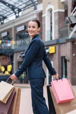 smiling attractive businesswoman carrying shopping bags and looking at camera