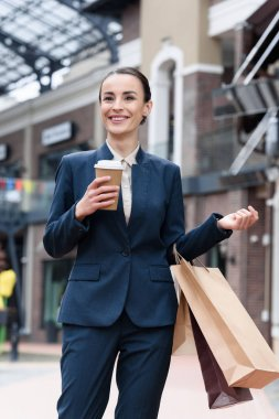 attractive businesswoman standing with disposable coffee cup and shopping bags