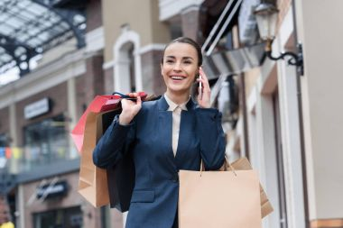 laughing attractive businesswoman talking by smartphone and holding shopping bags