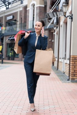 smiling attractive businesswoman walking form shopping and talking by smartphone