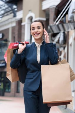 attractive businesswoman walking form shopping and talking by smartphone