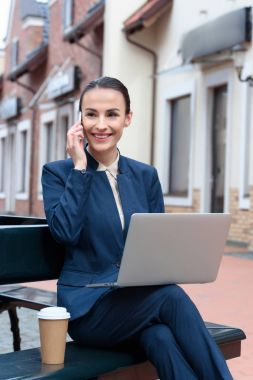 beautiful businesswoman talking by smartphone and using laptop