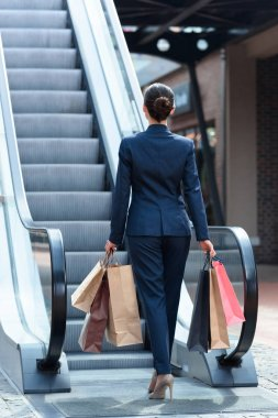 back view of businesswoman walking with shopping bags on escalator