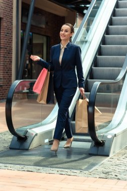 attractive businesswoman walking with shopping bags from escalator