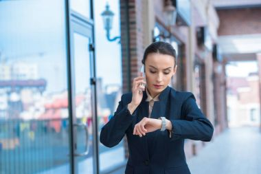 beautiful businesswoman checking time and talking by smartphone on street