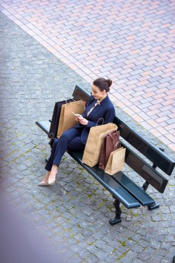 high angle view of attractive businesswoman sitting with shopping bags on bench and using smartphone