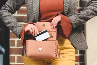 cropped image of stylish woman taking credit card from handbag