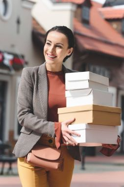 smiling attractive woman holding shopping boxes and looking away