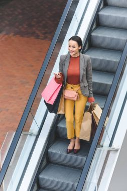 high angle view of attractive woman with shopping bags on escalator in mall