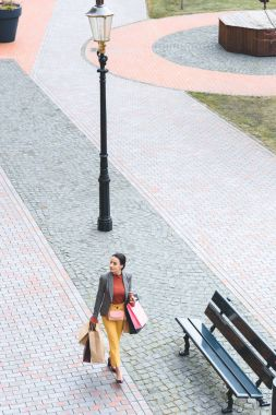 high angle view of attractive woman walking with shopping bags on street