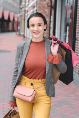 attractive woman holding shopping bags on shoulder and looking at camera