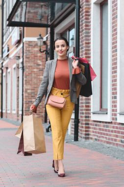 attractive woman walking with shopping bags on shoulder