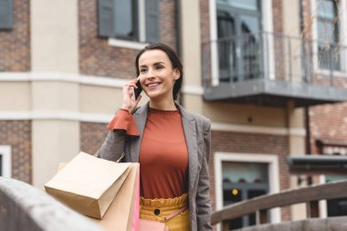 smiling woman walking after shopping and talking by smartphone