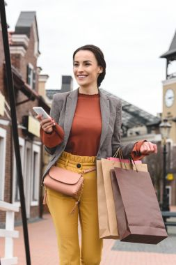 smiling woman walking with shopping bags and smartphone