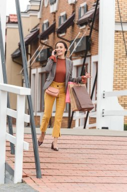 attractive woman walking from shopping and talking by smartphone