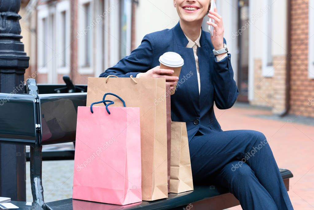 Cropped image of businesswoman talking by smartphone after shopping