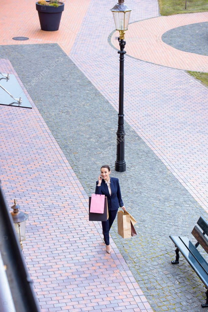 High angle view of attractive businesswoman walking with shopping bags and talking by smartphone