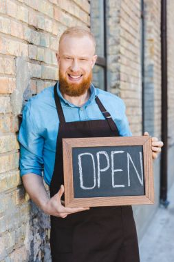 handsome bearded young barista holding sign open and smiling at camera