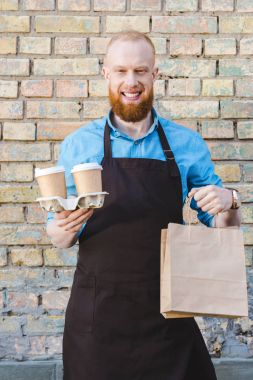 Smiling young male barista in apron holding paper cups of coffee in cardboard and papers bags stock vector