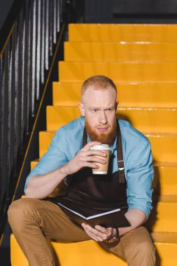 young male barista in apron drinking coffee from paper cup and holding textbook
