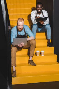 two young smiling owners of coffee shop in aprons with laptop and textbook sitting on stairs with paper cups of coffee