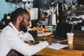 Fotografie smiling young african american barista in eyeglasses taking notes and using laptop with blank screen in cafe