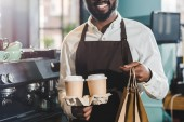 vágott lövés mosolyogva afro-amerikai barista papír táskák és eldobható kávéscsészét, kávézó