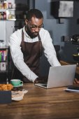 Fotografie mladí africké americké barista pomocí přenosného počítače při práci v kavárně