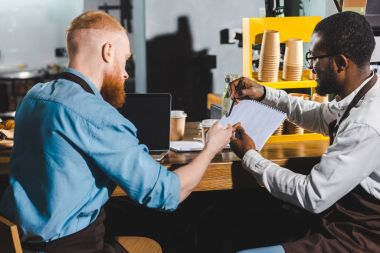 young african american male barista showing textbook to colleague in coffee shop